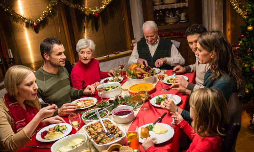 A family sitting at dinning table and eating Christmas dinner.