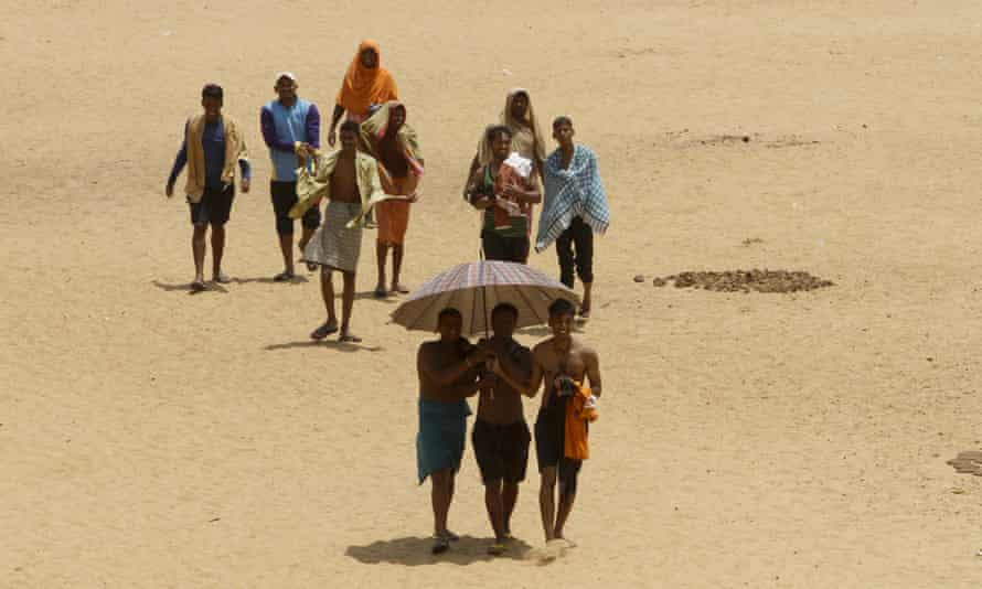 Villagers cover up in wet clothes as they walk back home after cooling off in the Daya river in Bhubaneswar, east India.