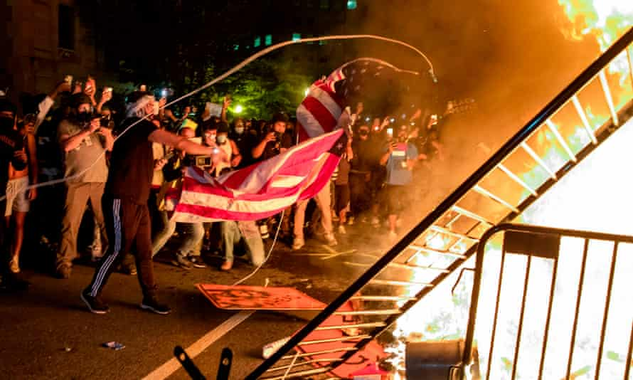 Protesters throw a US flag into a fire during a demonstration outside the White House.