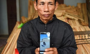 Nguyen Dinh Gia, father of 20-year-old Nguyen Dinh Luong, who is feared to be among the 39 people found dead, poses with his son's photograph at their house in Vietnam's Ha Tinh province.