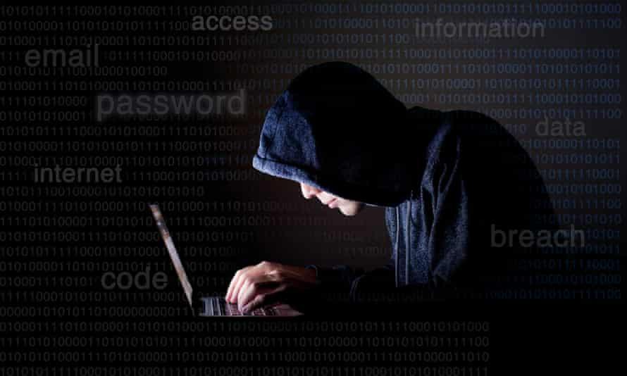 A hacker in a hoodie on a laptop