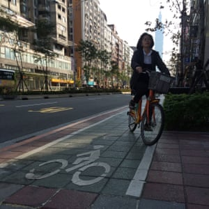 Cycling on a segregated pavement bike lane, with Taipei 101 tower in the background.