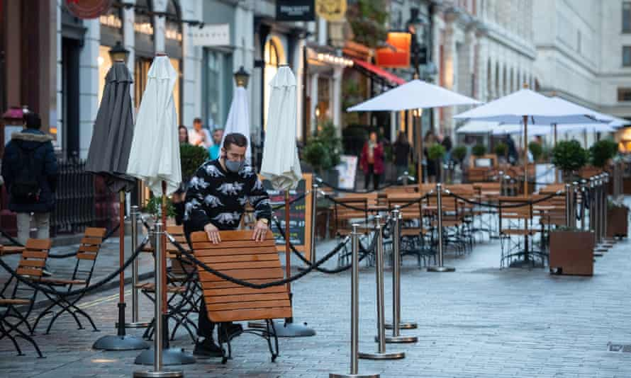 A man packs away tables and chairs outside a bar in Covent Garden, in central London.