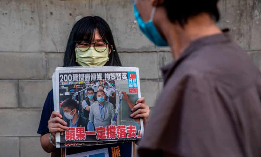 A woman holding a copy of the Apple Daily newspaper.