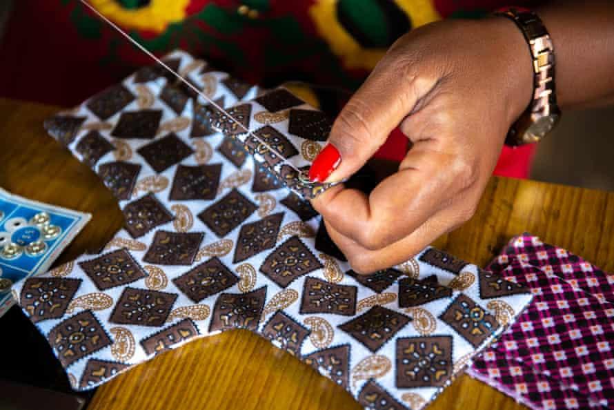 Sangita, 32, in Banepa municipality, Kavre district, Nepal, sews a button on to a reusable pad