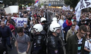 Serbian police flank demonstrators protesting new Covid-19 restrictions announced by the government in Belgrade.