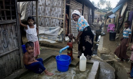 A Rohingya family collects water at a well at a camp outside Sittwe, in Burma's Rakhine state.