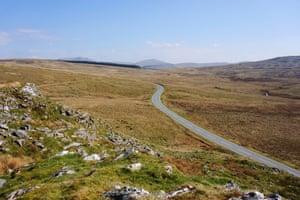 A road crossing the upland blanket bog and heathland vegetation of Migneint in Gwynedd, north Wales