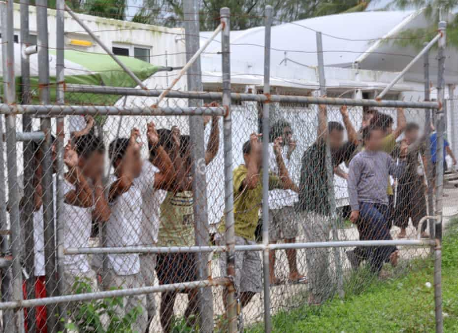 Asylum seekers behind a fence at the Manus Island detention centre, Papua New Guinea, in 2014.