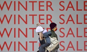 """Pedestrians walk past a """"Winter Sale"""" sign in the window display of a shop, closed down due to lockdown restrictions, on an empty Oxford Street on January 5, 2021."""