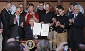 President Donald Trump, accompanied by coal miners and, from left, Interior Secretary Ryan Zinke, Environmental Protection Agency (EPA) Administrator Scott Pruitt, second from right, Energy Secretary Rick Perry, and Vice President Mike Pence, far right, holds up the signed Energy Independence Executive Order, Tuesday, March 28, 2017, at EPA headquarters in Washington.