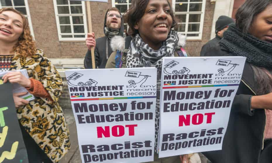 A woman holding two placards reading: 'money for education, not racist deportation'