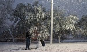 Tara Diamond builds a snowman in Ridgewood Park as snow falls in Corpus Christi, Texas