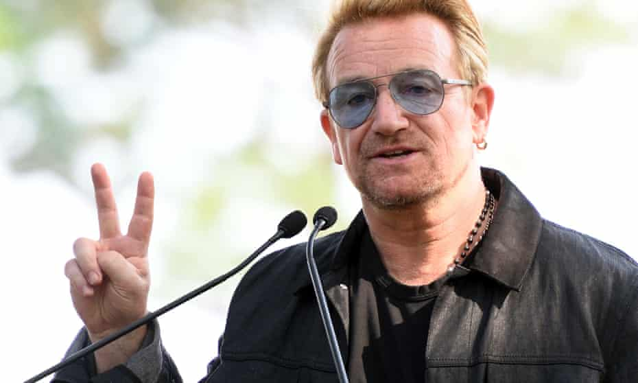 Bono holds up a peace sign during a dedication ceremony for a giant tapestry, from Amnesty International, in honor of John Lennon on Ellis Island July 29, 2015 in New York.