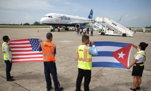 Ground crew hold US and Cuban flags after JetBlue flight 387 lands at Abel Santamaria international airport in Santa Clara, Cuba.