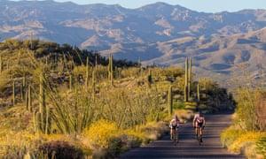 Couple road biking the Cactus Loop Road in Saguaro National Park, Arizona