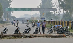 Sikh protesters use tree trunks and motorbikes to block the Amritsar-Delhi highway.