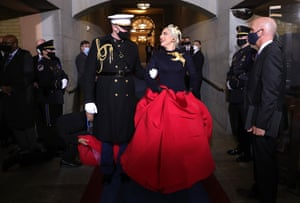 Lady Gaga is escorted by US marine Capt Evan Campbell before singing the national anthem at the inauguration of US President-elect Joe Biden.