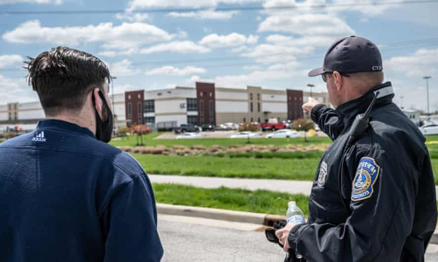 Police stand near a sign at the FedEx facility where multiple people were shot and killed the previous night in Indianapolis.