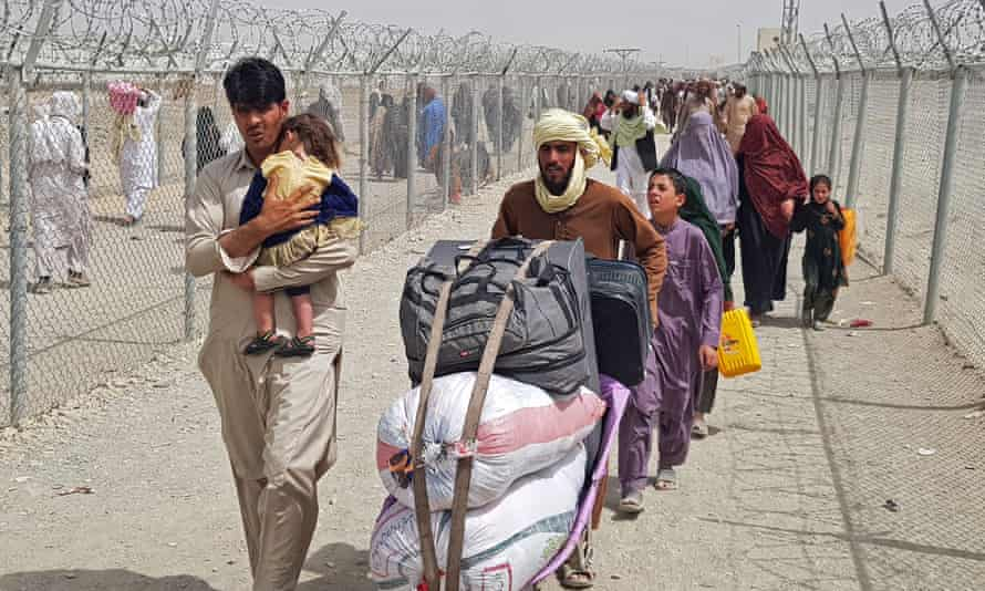 Afganos que cargan con sus hijos y bolsas de pertenencias caminan entre alambradas de púas en un cruce fronterizo
