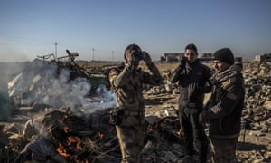 Iraqi soldiers stand near a fire on the main road from Erbil to Mosul on Wednesday. The US said it had launched an attack on a Mosul hospital where Isis fighters were operating.