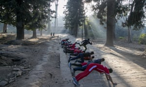 A Nepalese physical fitness trainer kicks a student as a form of punishment while they work out at a forest area near Pashupatinath Temple in Kathmandu, Nepal, Monday, Jan. 11, 2021. (AP Photo/Niranjan Shrestha)