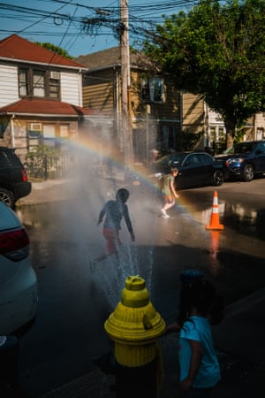 A group of children play in a stream of water from an uncapped fire hydrant in Corona, Queens.