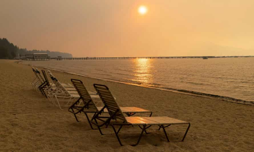 Empty chairs stand on the beach with the sky obscured by the smoke of the Caldor fire, in South Lake Tahoe, California, in August.