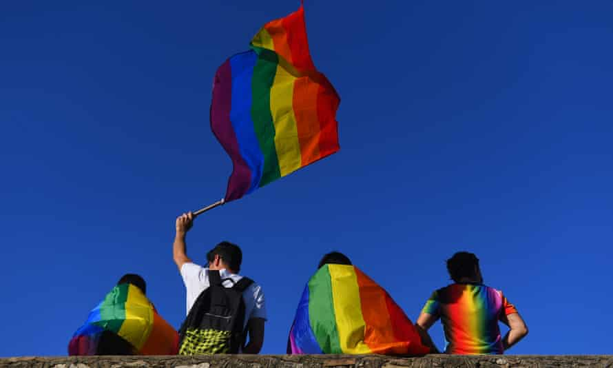 Four people with rainbow flags resting against a wall