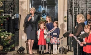 Theresa May outside Number 10 with the young winners who designed her official Christmas card.