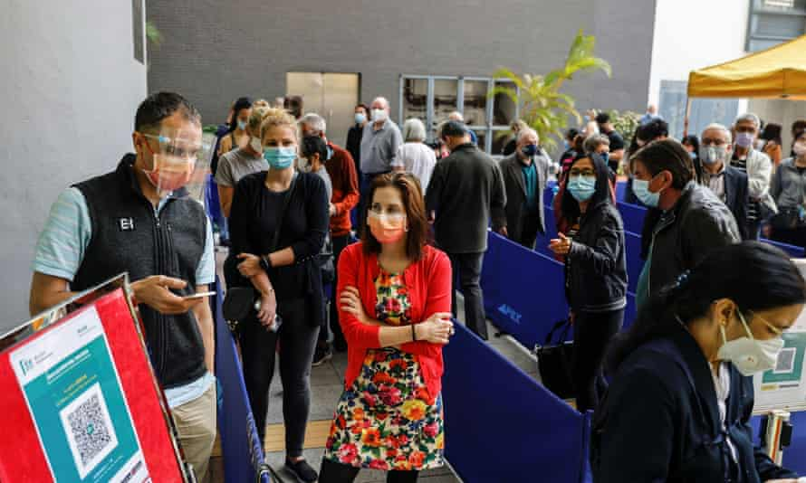 People queue up at a vaccination centre after Hong Kong suspended use of the Pfizer coronavirus vaccine.