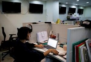 Oliver Emocling sits at his desk at a publishing company
