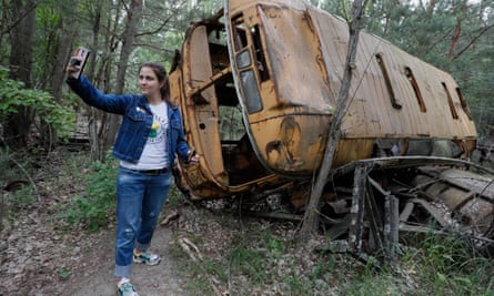 A visitor takes a selfie with an abandoned bus during a tour in Chernobyl