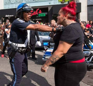 A female counter-protester argues with a police officer.
