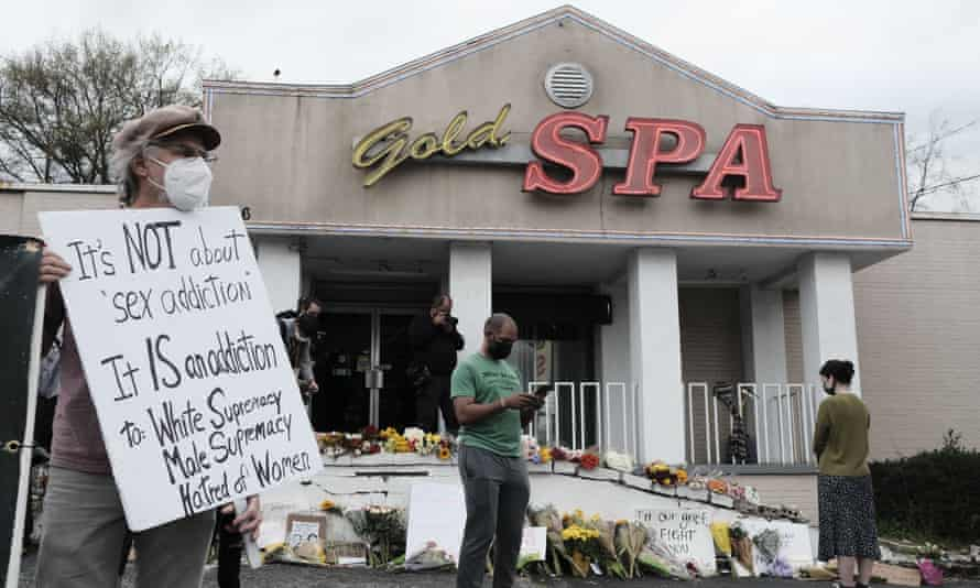 People hold signs and mourn the victims outside Gold Spa in Atlanta on March 18.