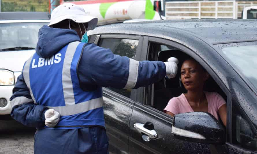 A Lesotho health official takes the temperature of motorists as a preventive measure against the spread of coronavirus
