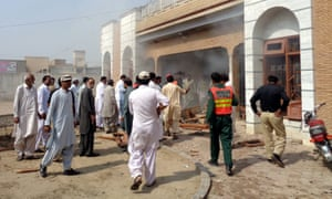 Rescue workers and people gather at the scene of a suspected suicide bomb attack