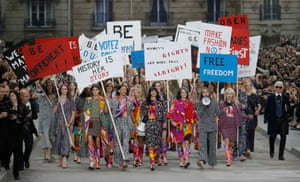 "Models walk ""Boulevard Chanel"", created by Lagerfeld for his Spring/Summer 2015 women's ready-to-wear show, which also saw them stage a feminist protest complete with placards"