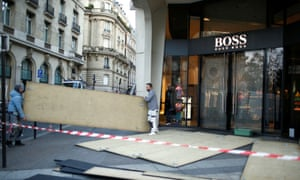 Workmen remove protective wood panels outside a store in central Paris on Sunday