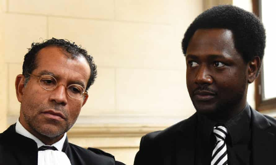 Souleymane Sylla (R) speaks to the press with his lawyer Jim Michel-Gabriel at the Palais de Justice.