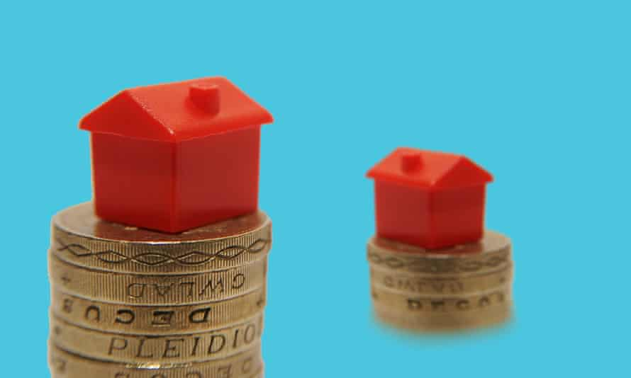 Some toy houses atop pound coins