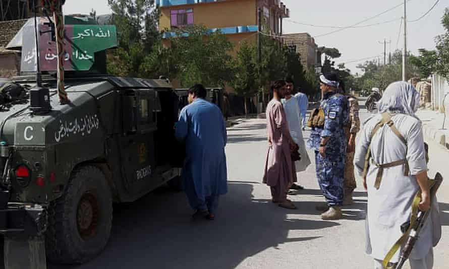 Afghan security personnel stand guard along a road in the western city of Qala-i- Naw.