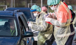 Medical assistants wearing protective clothing test a driver in Nuertingen, Germany