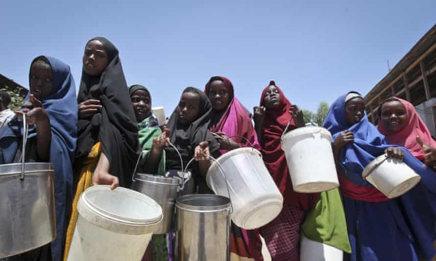 Girls who fled the drought in southern Somalia queue to receive food at a camp in Mogadishu