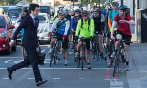 A man crosses the road in front of cyclists in London.