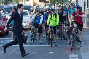 A commuter crosses in front of cyclists.