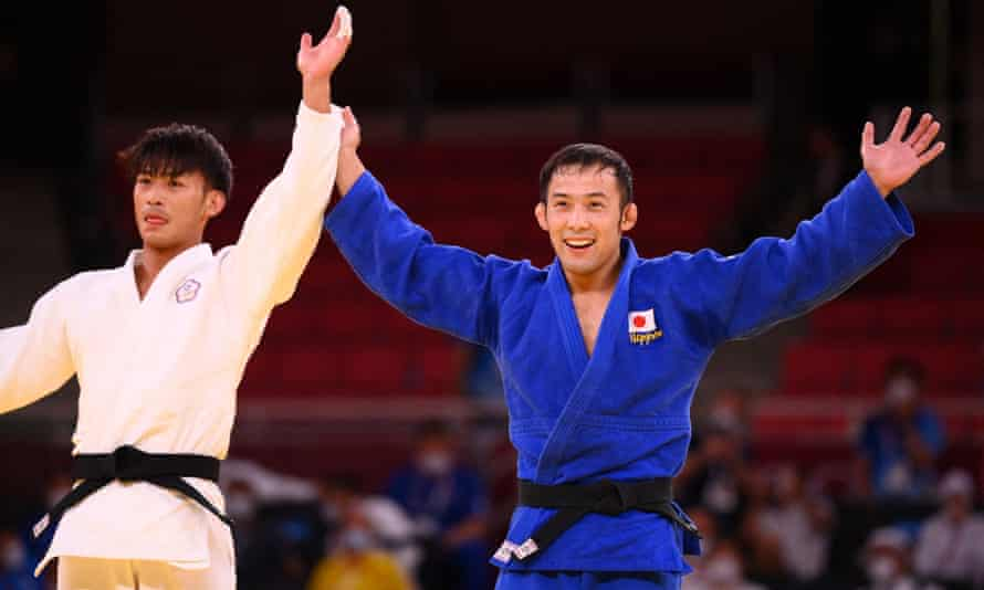Naohisa Takato, right, celebrates his win against Taiwan's Yang Yung-wei in the men's 60kg judo final.