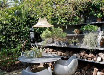 A table, chairs and a light in the garden's outdoor kitchen