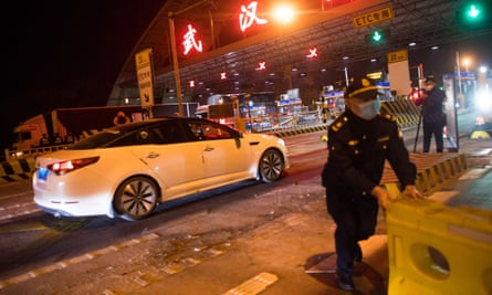 Barricades are removed from the road at an expressway toll station in northern Wuhan