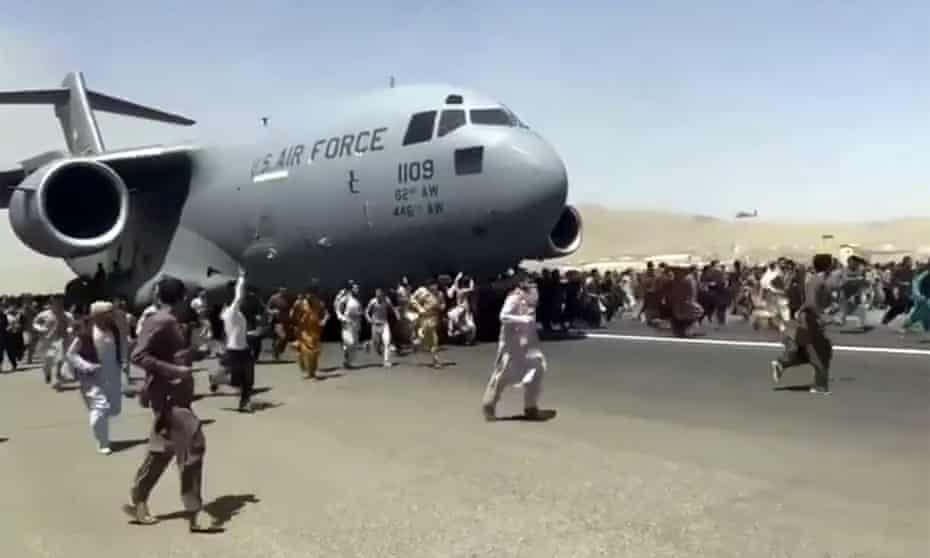 Afghans run beside a US Air Force transport plane as it tries to take off from Kabul, Afghanistan.